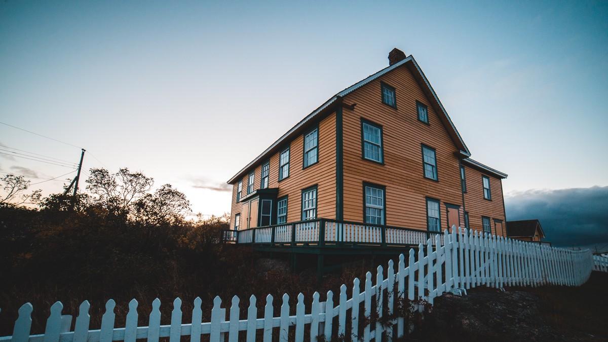 Dřevěný plot kolem krásného rodinného domu.