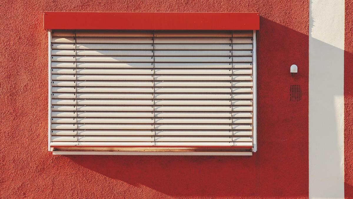 Světlá předokenní žaluzie na červené fasádě.