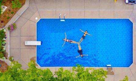 Zapuštěný zahradní bazén, ve kterém se koupou lidi.